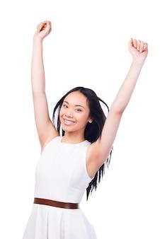 Udane piękno. piękna młoda azjatka w ładnej sukience z podniesionymi rękami i uśmiechnięta, stojąc na białym tle