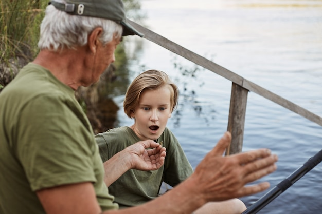 Udane wędkowanie, tata opowiada o dużych rybach do złowienia w letni weekend, dojrzały mężczyzna wędkarski na muchę, rybak z wnukiem, syn patrzy na ojca z otwartymi ustami i zdumionym wyrazem twarzy
