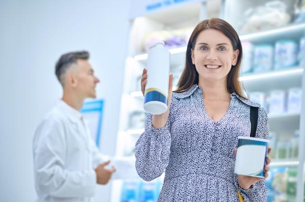 Udane zakupy. szczęśliwa młoda dorosła dobrze wyglądająca kobieta z zakupionymi materiałami medycznymi i męskim farmaceutą z tyłu apteki
