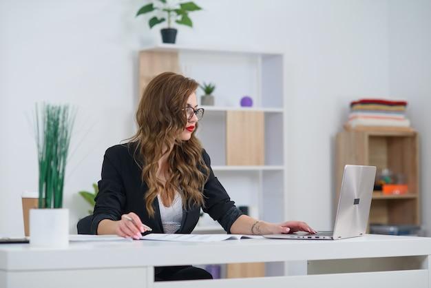 Udanego interesu w oficjalne ubrania siedzi w przytulnym jasnym biurze i pracuje z laptopem. koncepcja doświadczonego kierownika firmy.