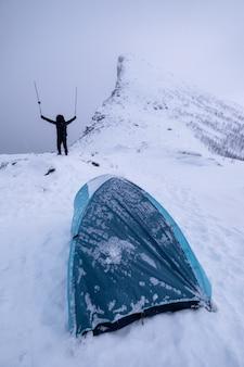 Udany alpinista stojący i podnoszący kijki trekkingowe na zaśnieżonym wzgórzu z namiotem biwakowym na szczycie w zamieci