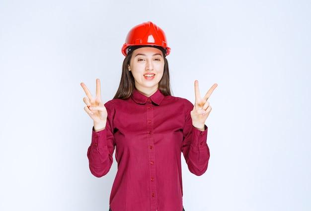 Udany architekt żeński w czerwonym kasku twardym stojąc i dając znak zwycięstwa.