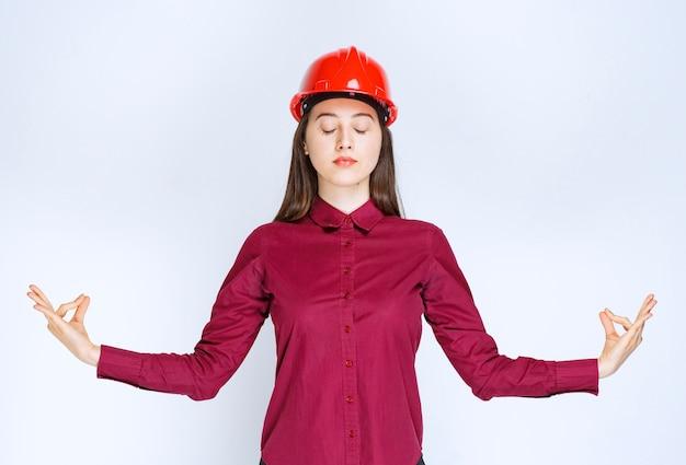 Udany architekt żeński w czerwonym kasku twardym, stojąc i robiąc medytację.