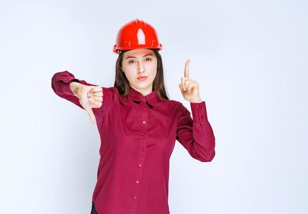 Udany architekt żeński w czerwonym twardym kasku stoi i daje kciuki w górę w dół.