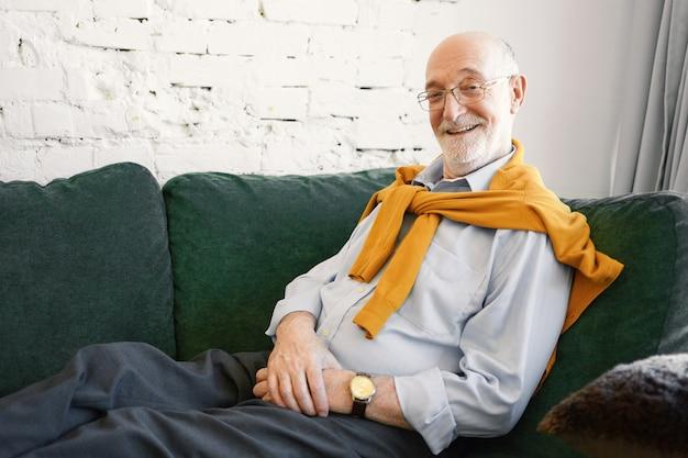 Udany atrakcyjny starszy biznesmen w okularach, formalnej koszuli i swetrze na szyi siedzi na kanapie w swoim biurze, z promiennym uśmiechem, szczęśliwy po dokonaniu dobrej transakcji