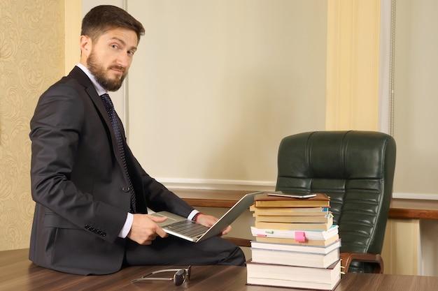 Udany biznes człowiek siedzi przy stole w biurze i pracy z laptopem