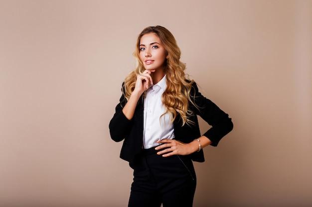 Udany biznes kobieta z szczerym uśmiechem i skrzyżowanymi rękami w stylowym garniturze na beżowej ścianie.