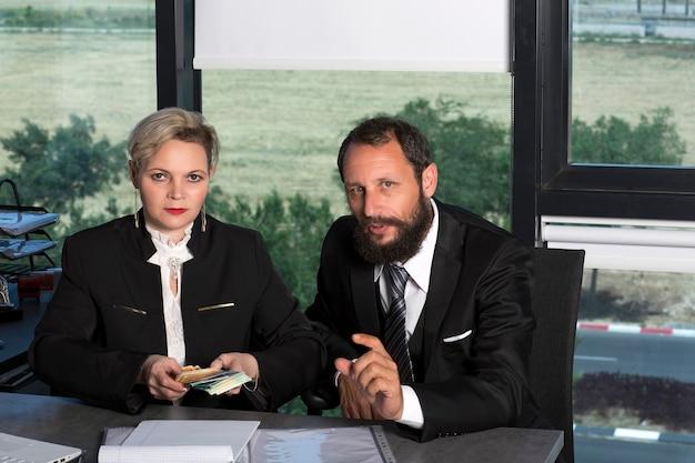 Udany biznes mężczyzna i kobieta liczyć pieniądze w nowoczesnym biurze. kaukaski pani liczenia pieniędzy przy stole. brodaty biznesmen w czarnym garniturze. para biznesowa pracująca, rozmawiająca razem nad projektem