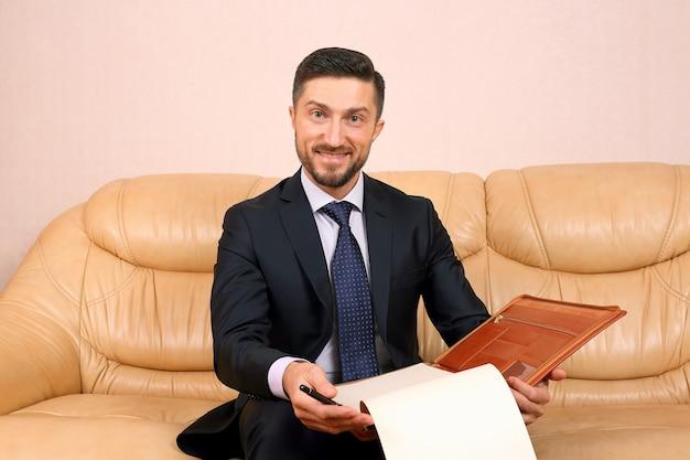 Udany biznes mężczyzna uśmiecha się z dokumentów biznesowych, siedząc na skórzanej kanapie