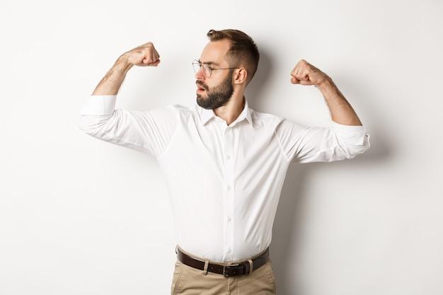 Udany biznesmen napina bicepsy, pokazuje mięśnie i wygląda pewnie, czuje się silny, stoi.