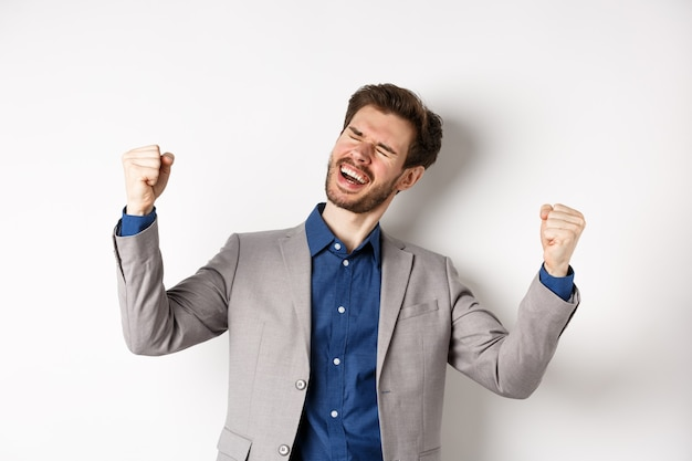 Udany biznesmen w garniturze, wygrywając nagrodę, krzycząc tak z ulgą uśmiechem i pompkami pięścią, świętując osiągnięcia i sukces, stojąc na białym tle.