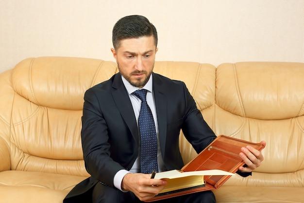 Udany biznesmen zaangażowany w dokumenty biznesowe, siedząc na skórzanej kanapie