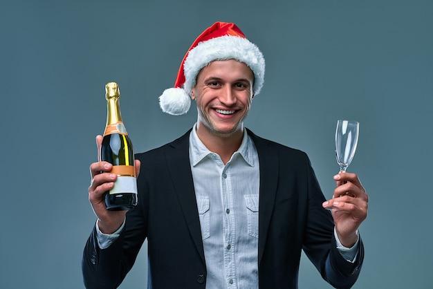 Udany człowiek w marynarce i świątecznym kapeluszu z butelką szampana świętuje nowy rok. studio fotograficzne na szarym tle.
