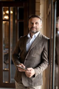Udany dojrzały elegancki biznesmen z tabletem, patrząc na ciebie, stojąc przed kamerą