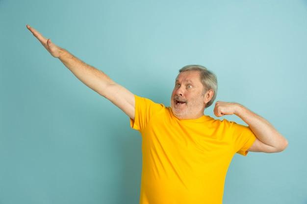 Udany gest zwycięzcy. portret kaukaski mężczyzna na białym tle na niebieskim tle studio. piękny męski model w żółtej koszuli pozowanie.