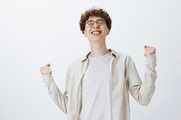 Udany i triumfujący nastoletni facet pozuje pod białą ścianą