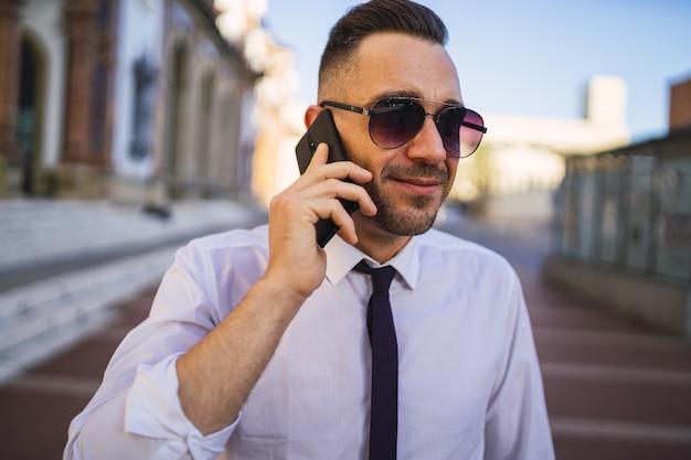 Udany młody biznesmen rozmawia przez telefon w formalnym stroju z okularami przeciwsłonecznymi