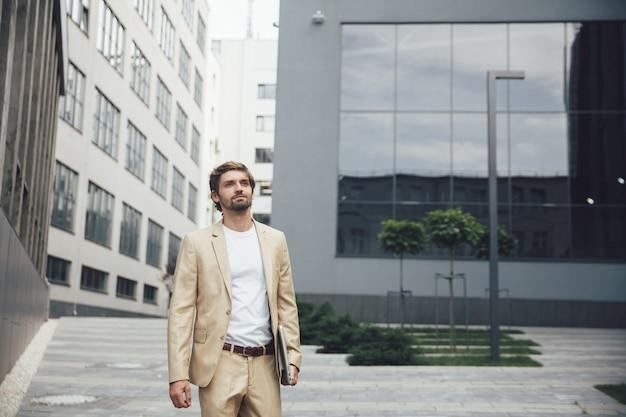 Udany młody biznesmen z poważnym wyrazem twarzy niosąc przenośny laptop w pobliżu ciemnego nowoczesnego budynku