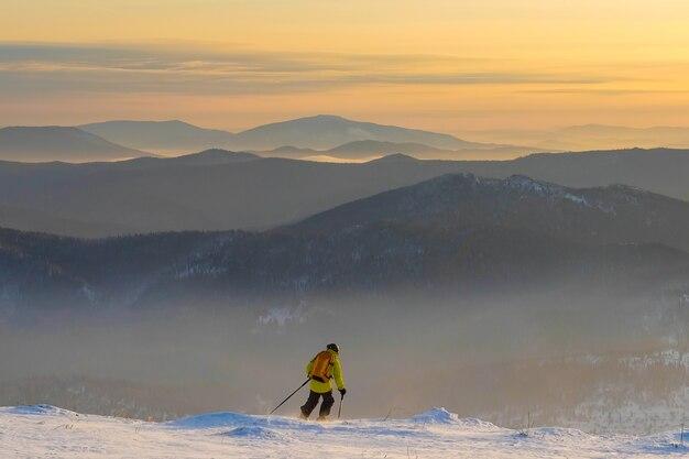 Udany młody człowiek na nartach w górach sheregesh. narciarz odpoczywa na szczycie góry.