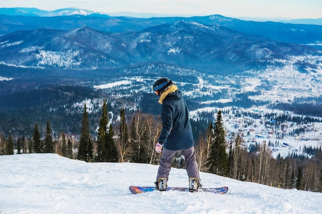Udany młody człowiek na snowboardzie w górach sheregesh. snowboardzista kaukaski