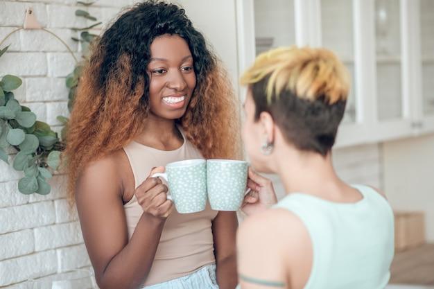 Udany poranek. ciemnoskóra szczęśliwa kobieta z długimi kręconymi włosami przy kawie i dziewczyną z tyłem do kamery komunikująca się w kuchni