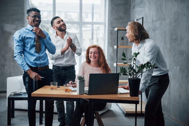 Udany projekt. młoda biznes drużyna pracuje nad projektem z laptopem na stołowym i uśmiechniętym