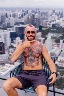 Udany przystojny europejski brodaty brutalny wytatuowany siłacz topless z zegarkiem siedzi na krześle na wysokim piętrze z niesamowitym widokiem na miasto