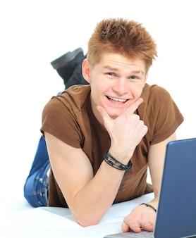 Udany szczęśliwy mężczyzna leżący na podłodze za pomocą laptopa