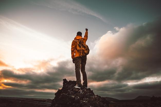 Udany turysta wędrujący na górę wskazującą na zachód słońca.