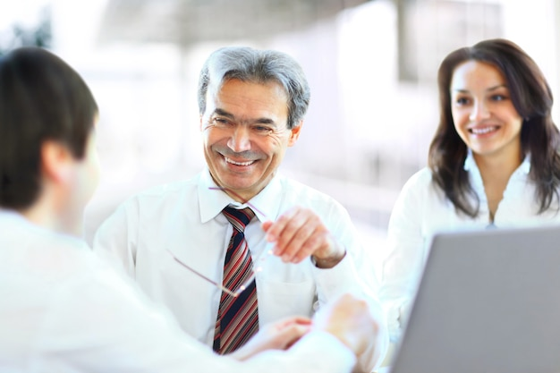 Udany zespół biznesowy składający się z trzech osób siedzących w biurze i planujących pracę