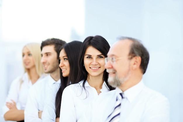 Udany zespół biznesowy stojący jeden za drugim w nowoczesnym biurze