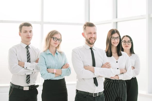 Udany zespół biznesowy stojący w jasnym biurze.zdjęcie z miejscem na kopię