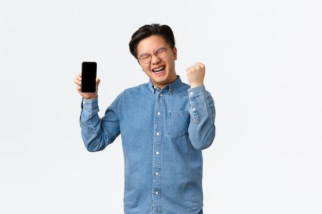 Udany zwycięski azjata w okularach i szelkach pokazujący ekran smartfona i pompkę pięści w triumf...