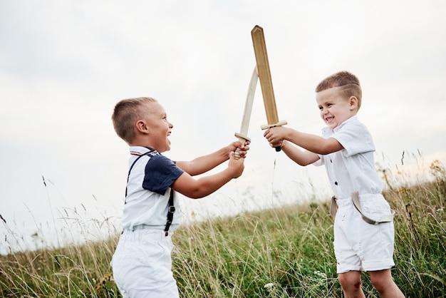 Udawaj, że jesteś prawdziwym mistrzem. dwoje dzieci, bawiąc się drewnianymi mieczami w polu