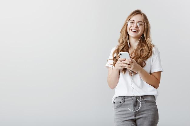 Udawanie, że cię słyszy podczas słuchania muzyki. portret atrakcyjnej stylowej europejskiej kobiety o blond włosach i okularach, uśmiechając się pozytywnie, trzymając smartfon i nosząc słuchawki na szarej ścianie