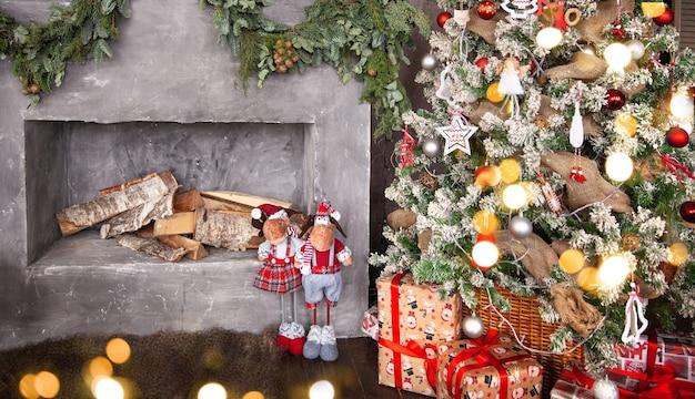 Udekorowana choinka przed ozdobnym kominkiem świąteczne wnętrze z choinką
