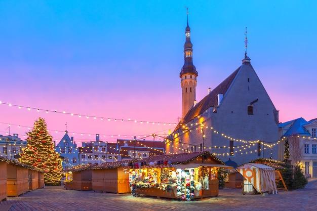 Udekorowana i oświetlona choinka i jarmark bożonarodzeniowy na placu ratuszowym lub na placykach raekoja o pięknym wschodzie słońca, tallinn, estonia.