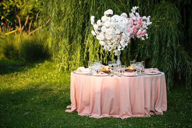 Udekorowany stół bankietowy na świeżym powietrzu ze świecami i suszonymi kwiatami