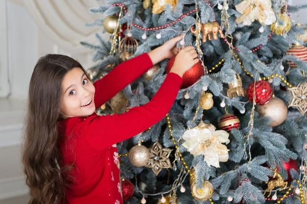 Udekoruj choinkę. szczęśliwa dziewczynka świętować ferie zimowe. szczęśliwego nowego roku. czas świąt. cute dziewczynka dziecko z prezentem xmas. dostawa prezentów świątecznych. ciesząc się imprezą sylwestrową.