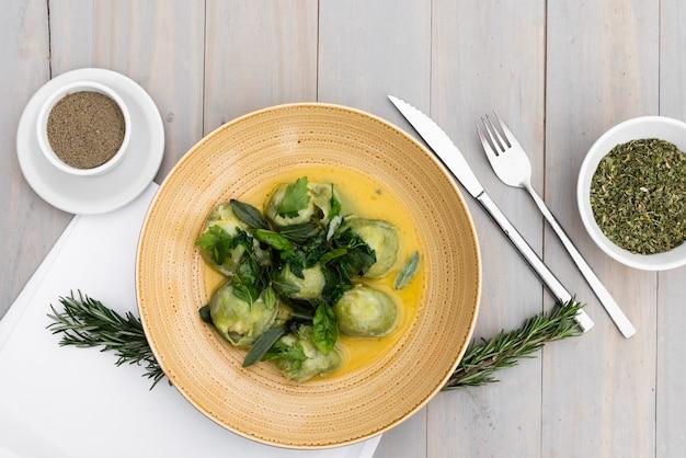 Udekoruj makaron ravioli z ziołami i przyprawami na drewnianym stole