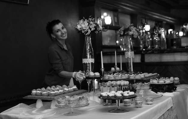 Udekoruj świąteczny stół słodyczami i różnymi słodkimi przekąskami na tle dziewczyny cukierniczej