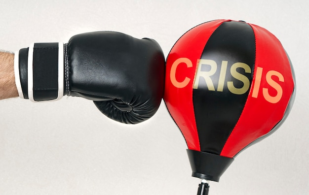 Uderz w koncepcję kryzysu ręką silnego mężczyzny w rękawicy bokserskiej, trafi w worek treningowy z tekstem kryzys.
