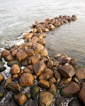 Uderzające fale morskie i skały leżące w pobliżu wybrzeża, letnia pogoda na wakacjach nad morzem