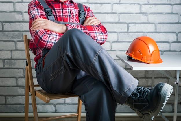 Uderzający pracownik w miejscu pracy. pracownik strajkujący na powierzchni ceglanego muru. odmowa pracy.