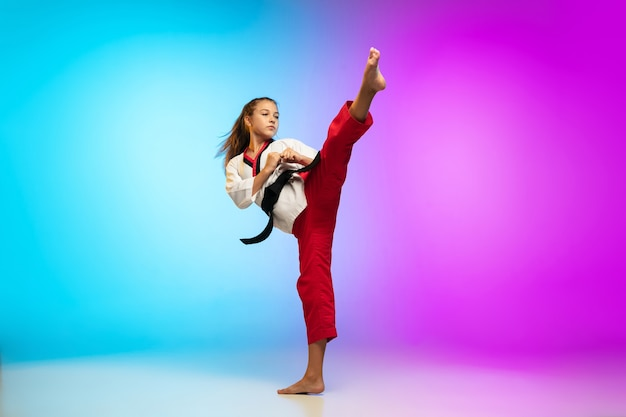 Uderzenie. karate, taekwondo dziewczyna z czarnym paskiem na białym tle na gradientowym tle w świetle neonowym. mały model kaukaski, dziecko sportowe trenujące w ruchu i akcji. sport, ruch, koncepcja dzieciństwa.