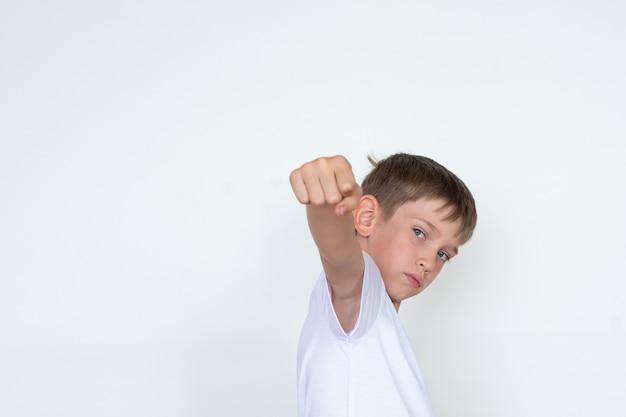 Uderzenie pięścią. chłopiec w białej koszulce z wyciągniętą ręką na białym