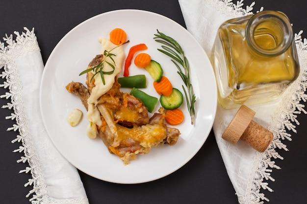 Udka królika zapiekane w białym winie z sosem beszamelowym na talerzu ceramicznym z warzywami i rozmarynem. butelka wina i serwetki na czarnym tle. dietetyczne mięso królika gotowane w piecu. widok z góry.