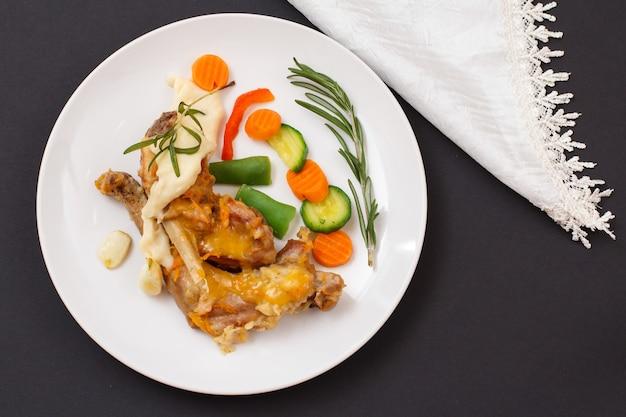 Udka królika zapiekane w białym winie z sosem beszamelowym, warzywami i rozmarynem na talerzu ceramicznym z serwetką na czarnym tle. dietetyczne mięso królika gotowane w piecu. widok z góry.
