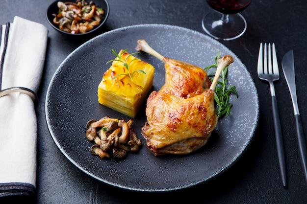 Udka z kaczki confit z zapiekanką ziemniaczaną i grzybami na talerzu.