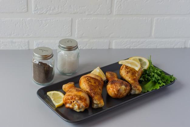 Udka z kurczaka z przyprawami, rozmarynem i limonką na szarym tle. skopiuj miejsce.